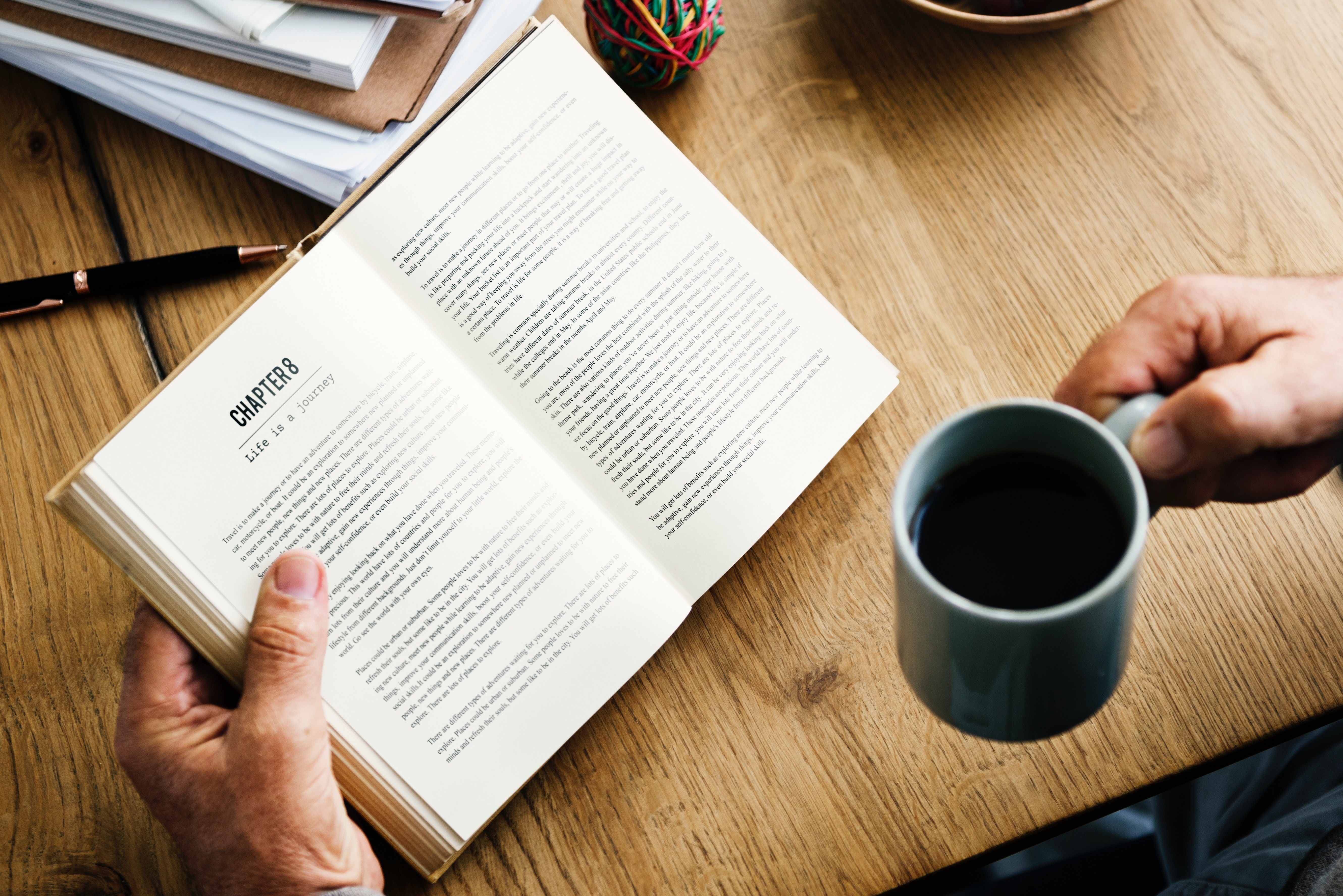 hands holding book and coffee mug
