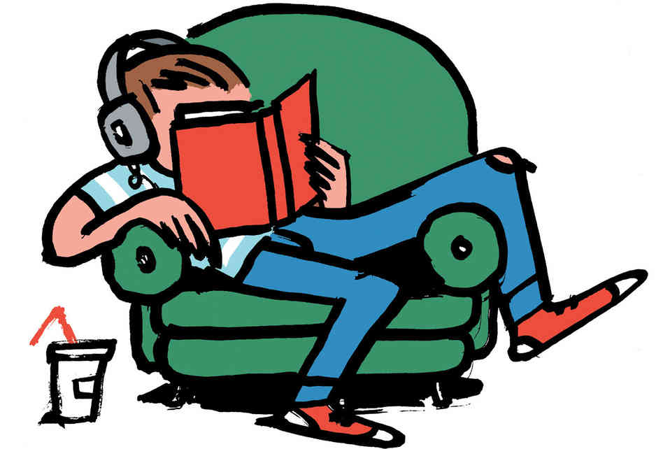 Teen with headphones reading a book in a recliner