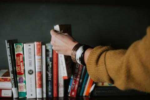 hand reaching for books on shelf