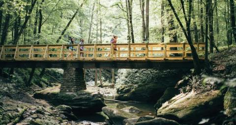 Image of hikers going across a bridge